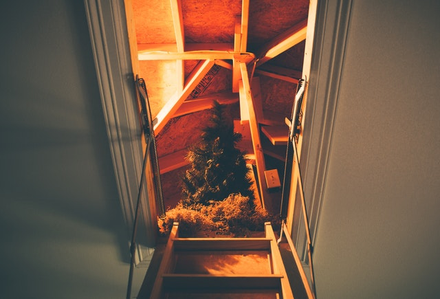 ladder going up to attic with christmas tree in storage